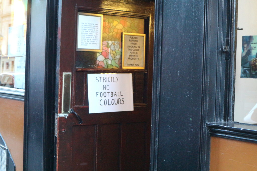 """No Football Colors Allowed"" reads a sign outside of a bar in Scotland."